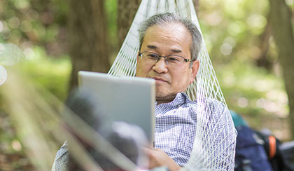 Man viewing tablet device while laying in hammock.