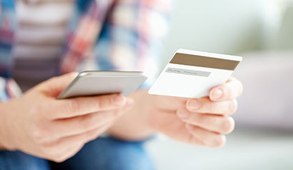 Person holding credit card and using smartphone.