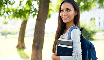A college student walking on campus holding books.